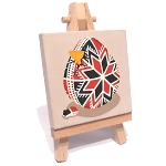 A mini canvas on easel painted with a black and red pysanka